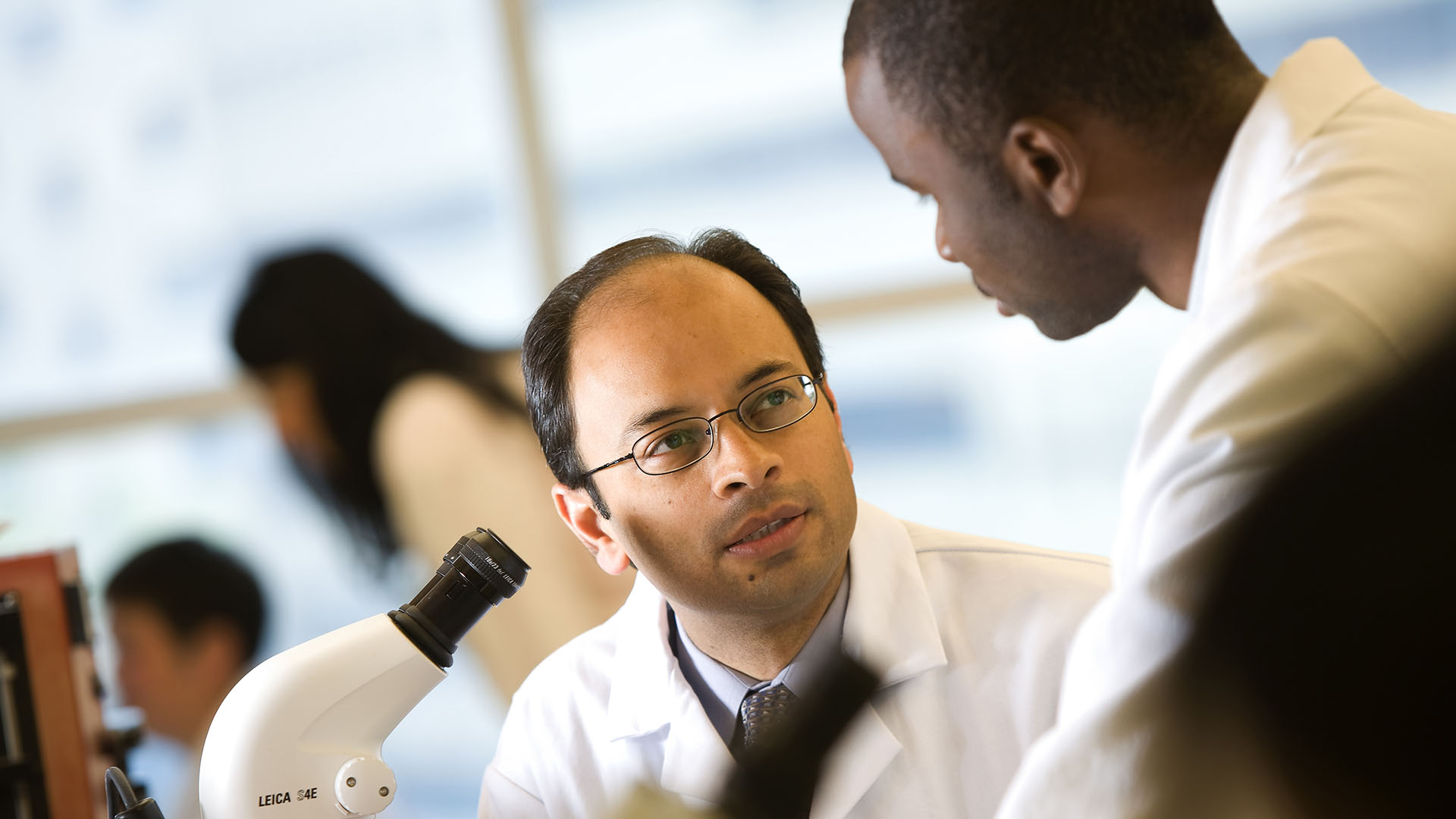 Dr. Mukesh Jain interacts with a young male colleague at a microscope.