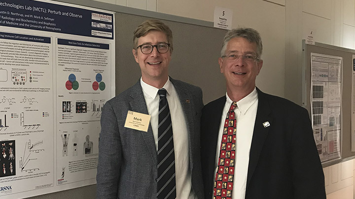 Dr. PJ Utz stands in front of a scientific poster with a male young physician-scientist.