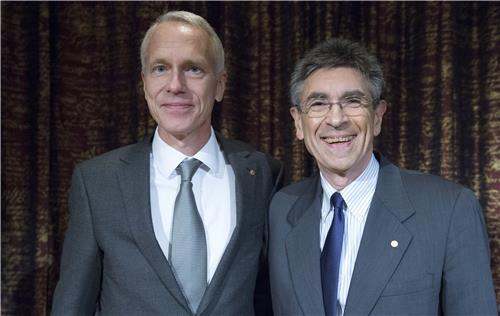 Drs. Brian Kobilka and Robert Lefkowitz stand together at an event.